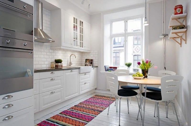 Кухня в белых тонах, на столе тюльпаны в вазе