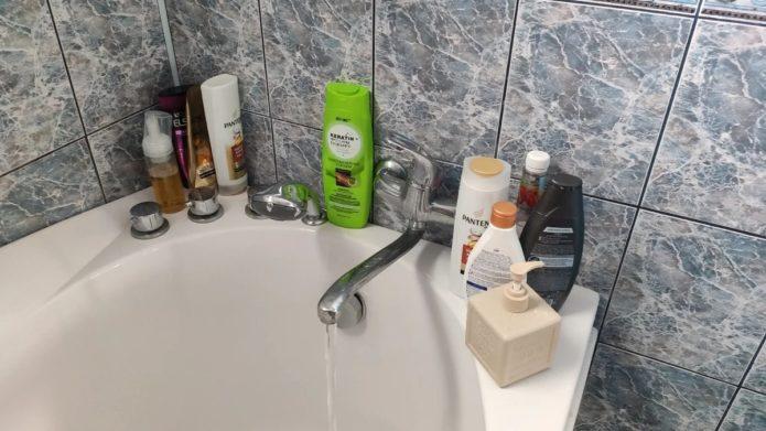 бортики ванны заставлены шампунями
